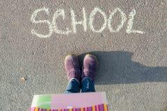 La escuela de la palabra en el asfalto y los pies del estudiante Foto de archivo libre de regalías