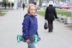 La escuela feliz envejeció a la muchacha rubia en un paseo con un monopatín en la ciudad Foto de archivo libre de regalías