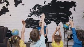 La escuela primaria del profesor en vidrios durante la lección comprueba el conocimiento de sus alumnos que aumenten sus manos pa almacen de video