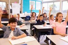 La escuela primaria embroma en una sala de clase que aumenta sus manos imagen de archivo libre de regalías
