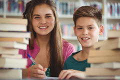 La escuela sonriente embroma hacer la preparación en biblioteca en la escuela Fotos de archivo