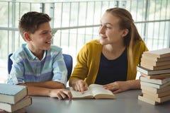 La escuela sonriente embroma los libros de lectura en biblioteca en la escuela Fotos de archivo