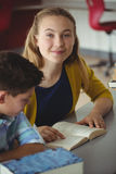 La escuela sonriente embroma los libros de lectura en biblioteca en la escuela Fotografía de archivo libre de regalías