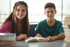 La escuela sonriente embroma los libros de lectura en biblioteca en la escuela Imagen de archivo