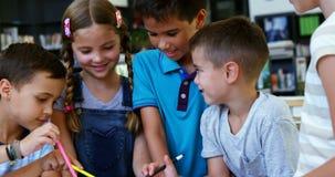 La escuela sonriente embroma usando la tableta digital en sala de clase almacen de video