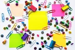 La escuela y los materiales de oficina coloridos empapelan los clips, pernos, notas amarillas, etiquetas engomadas en el fondo bl foto de archivo