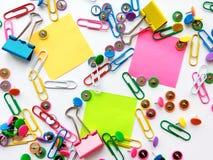 La escuela y los materiales de oficina empapelan los clips, pernos, notas, etiquetas engomadas en el fondo blanco fotos de archivo libres de regalías