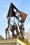 La escultura de la gente que lleva la bandera olímpica Fotos de archivo