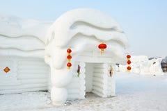 La escultura de nieve - casa popular blanca y luz roja Imagen de archivo libre de regalías