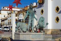 La escultura del hombre con los leones en el cuadrado central de la ciudad adornado con la Navidad juega Imagen de archivo libre de regalías