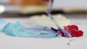 La espátula del pintor para dibujar, mezcla el primer del color azul y rojo almacen de video