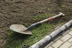 La espada que cultiva un huerto en hierba y estiércol vegetal, alista a la estación de primavera Imágenes de archivo libres de regalías