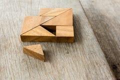 La espera del rompecabezas del rompecabezas chino para satisface a la forma del corazón en la tabla de madera Imagen de archivo libre de regalías