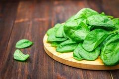 La espinaca jugosa fresca se va en una tabla marrón de madera Productos naturales, verdes, comida sana, vitaminas Imágenes de archivo libres de regalías