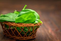 La espinaca jugosa fresca se va en una tabla marrón de madera Productos naturales, verdes, comida sana, vitaminas Imagenes de archivo