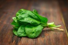 La espinaca jugosa fresca se va en una tabla marrón de madera Productos naturales, verdes, comida sana, vitaminas Imagen de archivo