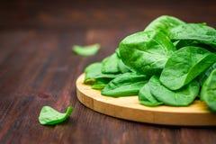 La espinaca jugosa fresca se va en una tabla marrón de madera Productos naturales, verdes, comida sana, vitaminas Imagen de archivo libre de regalías