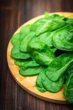 La espinaca jugosa fresca se va en una tabla marrón de madera Productos naturales, verdes, comida sana, vitaminas Fotos de archivo libres de regalías