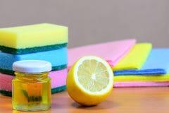 La esponja de la limpieza con friega y los trapos fijados, aceite de oliva en el tarro de cristal, limón medio en una tabla de ma Imagen de archivo