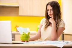 La esposa de la mujer joven en concepto del planeamiento del presupuesto foto de archivo