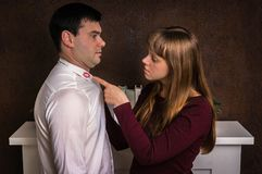 La esposa finded el lápiz labial rojo en el cuello de la camisa - concepto de la infidelidad foto de archivo