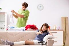La esposa herida pierna de ayuda del marido en quehacer doméstico fotografía de archivo