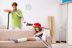 La esposa herida pierna de ayuda del marido en quehacer dom?stico fotos de archivo libres de regalías