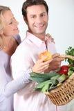 La esposa toma la manzana de la cesta. Foto de archivo libre de regalías