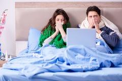 La esposa y el marido enfermos en cama con el ordenador portátil imágenes de archivo libres de regalías