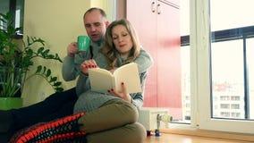 La esposa y el marido preciosos pasaron el tiempo junto cerca del radiador caliente en día frío almacen de metraje de vídeo