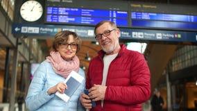 La esposa y el marido se est?n colocando con los pasaportes en la plataforma del ferrocarril Familia feliz, riendo y bromeando almacen de video
