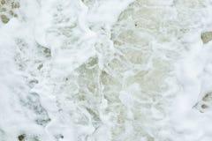 La espuma blanca causó a por la acción de la onda Fotografía de archivo