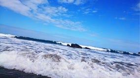 La espuma blanca nace de un mar azul intenso Imagen de archivo libre de regalías