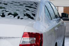 La espuma para lavar el coche fluye abajo de la parte posterior del coche Fotos de archivo
