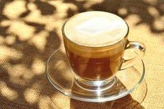 La espuma remató el Latte en la taza de café de cristal Imagen de archivo