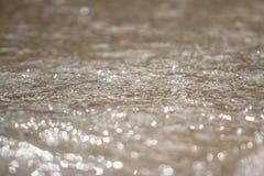 La espuma y la arena burbujeantes del mar en la playa Imágenes de archivo libres de regalías