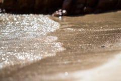 La espuma y la arena burbujeantes del mar en la playa Fotos de archivo