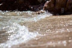 La espuma y la arena burbujeantes del mar en la playa Imagen de archivo libre de regalías
