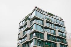 La esquina del edificio con muchas ventanas contra el cielo gris Fotografía de archivo libre de regalías