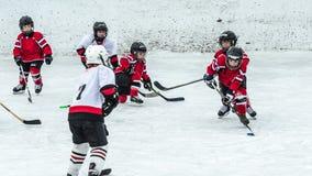 La estación de hockey, niños juega al juego nacional en un carnaval del invierno Fotografía de archivo libre de regalías