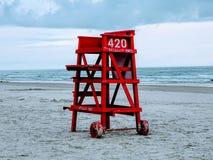 La estación del salvavidas en el océano azul abandonado de la playa se nubla la arena Imagenes de archivo