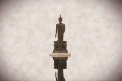La estatua budista en el agua refleja Foto de archivo libre de regalías