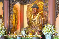 La estatua budista en templo adornó las luces, flores coloridas en cumpleaños del ` s de Buda Imagen de archivo libre de regalías