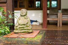 La estatua de Buda hizo de piedra con el musgo Imagenes de archivo