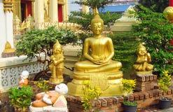 La estatua de Buda y los pequeños monjes de risa acercan al templo budista Imagenes de archivo