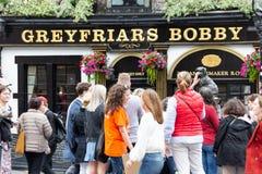 La estatua de Greyfriars Bobby delante del Pub en Edimburgo tocó para la suerte del turista fotos de archivo libres de regalías