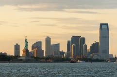 La estatua de la libertad contra el horizonte de New Jersey en puesta del sol foto de archivo