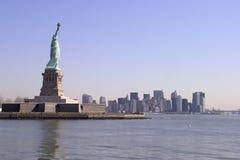 La estatua de la libertad y de un horizonte más inferior de Manhattan - Nueva York Imagenes de archivo