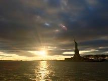 La estatua de la libertad se coloca entre un paisaje dramático imagen de archivo