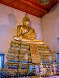 La estatua de oro de Buda se está sentando en el templo con el techo rojo Imagen de archivo libre de regalías